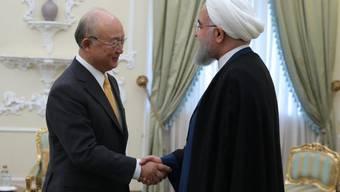 Irans Präsident Hassan Ruhani (r) begrüsst in Teheran IAEA-Chef Yukiya Amano