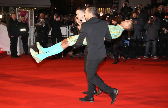 Spassvogel: Der belgischer Singer-Songwriter Stromae lässt sich von zwei Bodygards über den roten Teppich tragen.