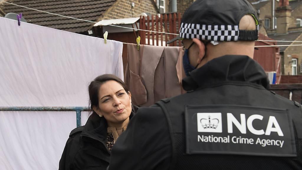 ARCHIV - Priti Patel (l), Innenministerin von Großbritannien, nimmt an einem Einsatz der National Crime Agency im Osten Londons teil. Foto: Stefan Rousseau/PA Wire/dpa