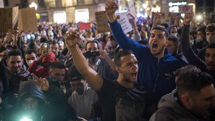 Demonstranten rufen Parolen gegen die Regierung bei einem Protest gegen die neuen Anti-Corona-Massnahmen. Bei dem Protest kam es zu Zusammenstößen mit der Polizei. Die Demonstranten protestierten gegen die Schließung von Bars, Restaurants und anderen Geschäften inmitten der Corona-Pandemie. Foto: Emilio Morenatti/AP/dpa