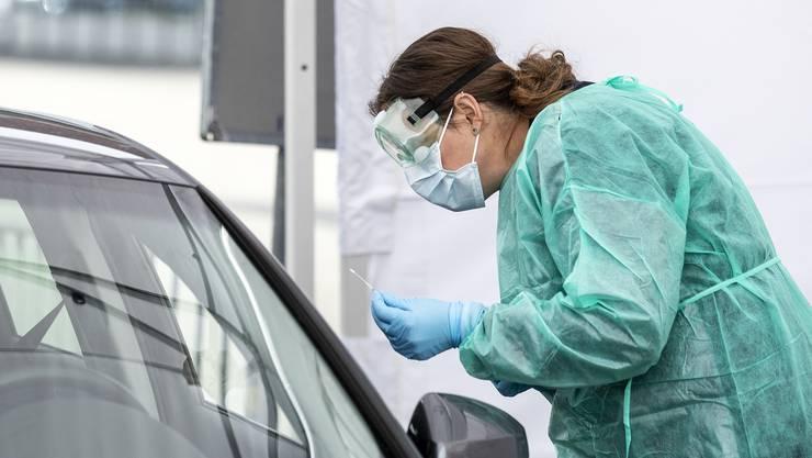 Der Rachenabstrich wird im Drive-In-Testcenter in Luzern durch das geöffnete Autofenster gemacht.