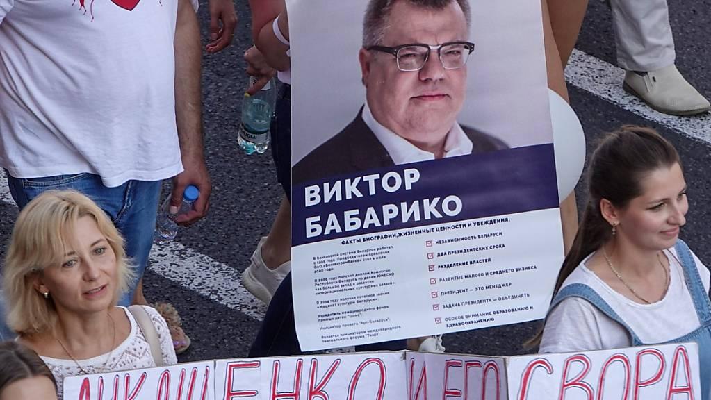 ARCHIV - Menschen tragen bei einer Demonstration gegen Machthaber Lukschenko ein Transparent mit dem Foto von Viktor Babariko. Foto: Ulf Mauder/dpa