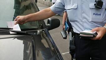 Ein Mitarbeiter der Stadtpolizei Zürich verteilt Strafzettel wegen Falschparkens (Archiv)