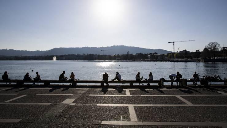 Menschen geniessen das frühlingshafte Wetter am Zürichsee.