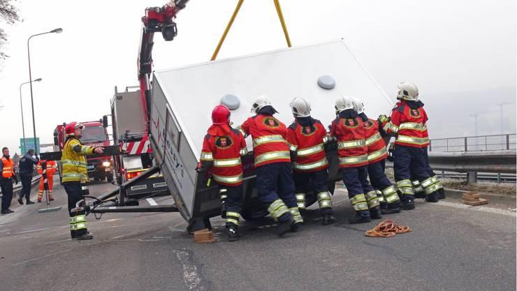 Feuerwehrmänner richten den umgekippten Hundetransporter wieder auf.