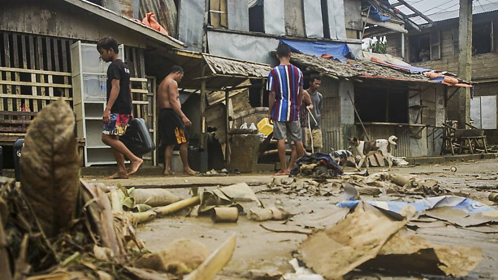 Anwohner räumen Trümmer von den Überschwemmungen durch den Taifun «Surigae» auf. Foto: Uncredited/AP/dpa