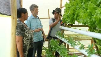 Emile Stricker (Mitte) im Gespräch mit Quartierbewohnern und World-Vision-Mitarbeitern zum neusten Projekt, das Landlosen neben ihrem Haus erlaubt, in Hydrokultur Salat zu produzieren, um die Ernährung ihrer Kinder und ihr Einkommen aufzubessern.