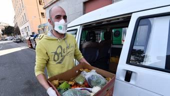 Botendienst in schwierigen Zeiten: Ein freiwilliger Helfer liefert in Genua Essen aus.