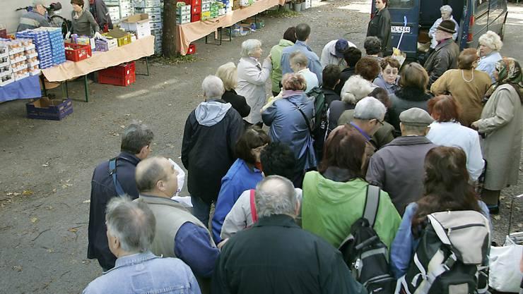 """Bedürftige Menschen stehen beim gemeinnützigen Verein """"Münchner Tafel"""" Schlange und warten auf die Verteilung kostenloser Lebensmittel. Über 15 Millionen Menschen in Deutschland leben an der  Armutsgrenze. (Archiv)"""