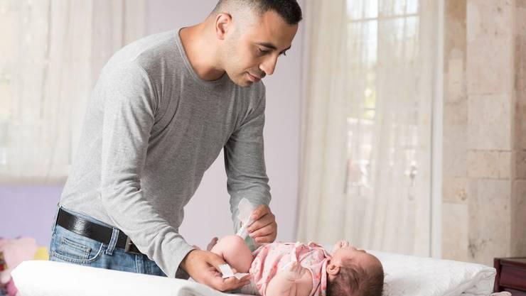 Mann wickelt sein Kind.