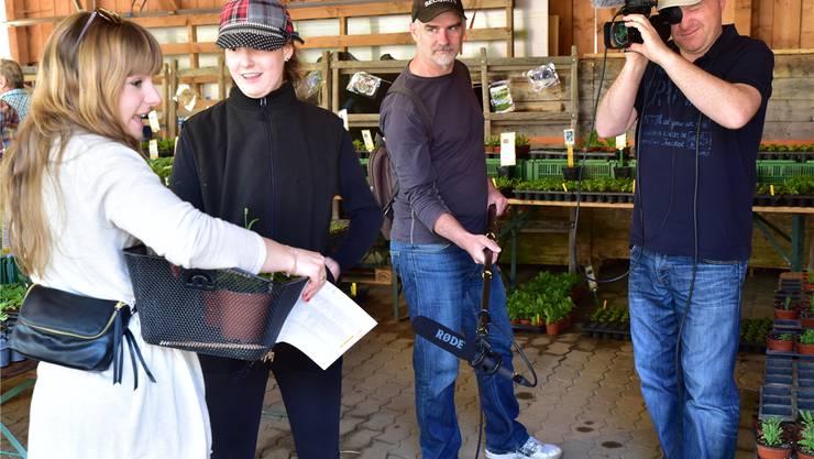 Buechehof-Bewohnerin Irina (2. v.l.) mit Kundin am Bio-Setzlingsmarkt vom 7. Mai, beobachtet von Kameramann Peter Schurte (r.) und Peter Bolliger.