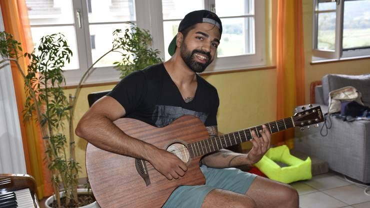 Luke Tasci greift zu Hause in die Gitarrensaiten.