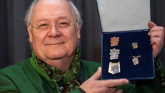 """Der Basler Gestalter Kurt Walter mit den von ihm entworfenen Fasnachtsplaketten. Das Motto der Basler Fasnacht 2020 lautet """"Heb di fescht""""."""