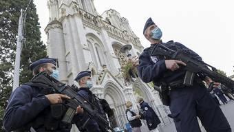 Polizisten stehen nach einer Messerattacke in der Nähe der Kirche Notre-Dame Wache. Bei der Messerattacke hat es mindestens drei Tote und mehrere Verletzte gegeben. Die Pariser Anti-Terror-Staatsanwaltschaft hat die Ermittlungen übernommen. Frankreich hat die höchste Terrorwarnstufe ausgerufen. Foto: Eric Gaillard/Pool Reuters/AP/dpa