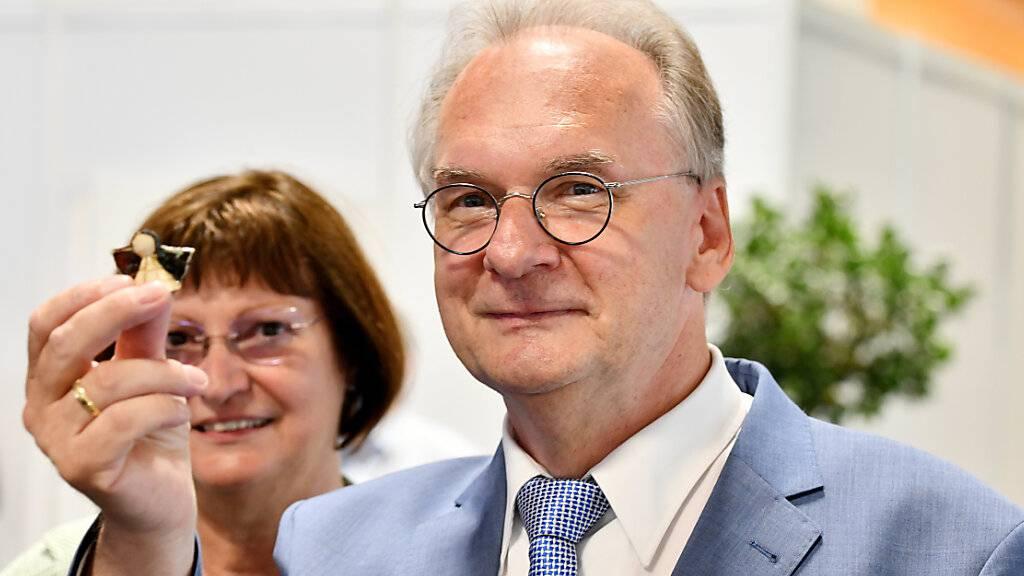 Sachsen-Anhalts amtierender Ministerpräsident Reiner Haseloff (CDU) zeigt einen Glücksbringer. Nach ersten Prognosen zeichnet sich ein klarer Sieg der regierenden Christdemokraten ab. Die Wahl gilt als wichtiger Stimmungstest vor der Bundestagswahl im September.
