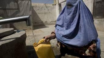 Eine Afghanin füllt Trinkwasser in einen Kanister: An einer Schule wurden Dutzende Schülerinnen mit Trinkwasser vergiftet (Symbolbild)