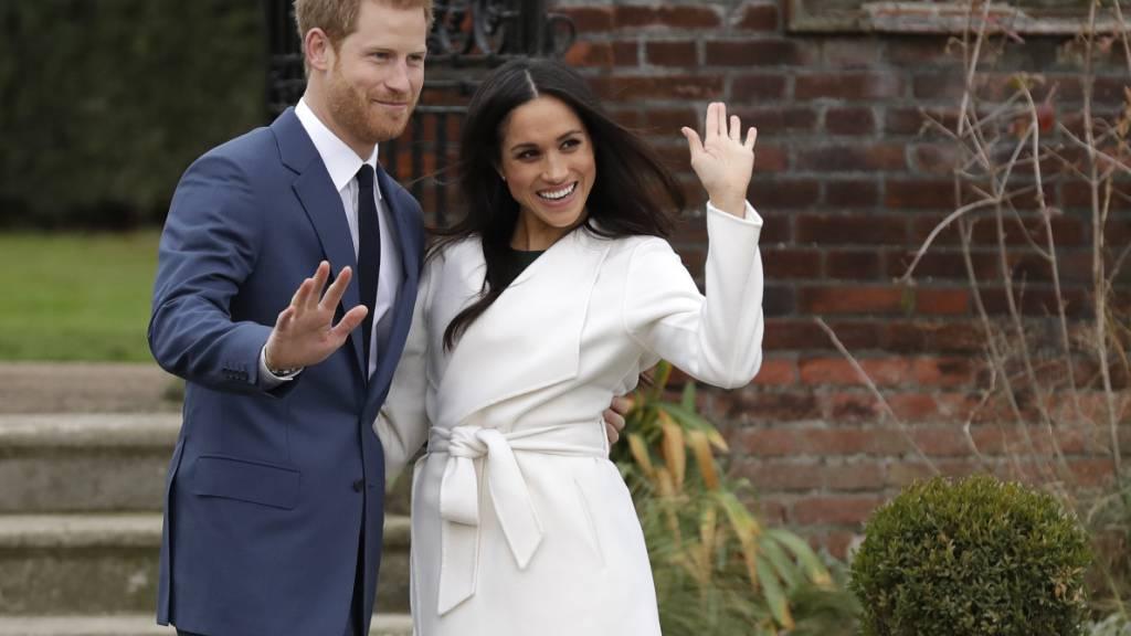 ARCHIV - Der britische Prinz Harry und die US-amerikanische Schauspielerin Meghan Markle winken nach Bekanntgabe ihrer Verlobung auf dem Gelände des Kensington Palace. Harry und Meghan sind nun zum zweiten Mal Eltern geworden. Foto: Matt Dunham/AP/dpa