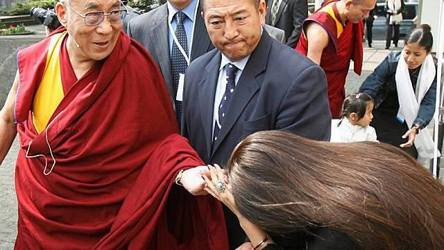 Eine Frau begrüsst den Dalai Lama in Zürich vor der Medienkonferenz