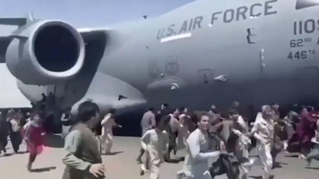 Verzweifelte Menschen rennen auf dem Flughafen von Kabul neben einer amerikanischen Militärmaschine her. Einige versuchten sich daran festzuhalten. Die US-Luftwaffe hat «menschliche Überreste» im Fahrwerkschacht der Maschine entdeckt.