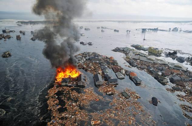 Brennende Häuser schwimmen in den Wasser- und Geröllmassen mit, als wären sie Spielzeug