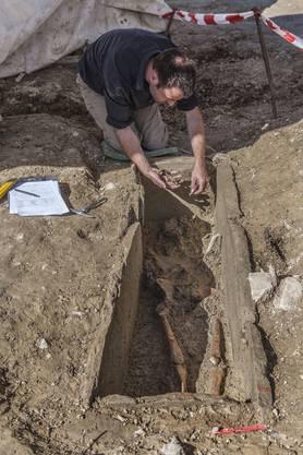 Ein Archäologe legt in Seengen ein Grab frei.