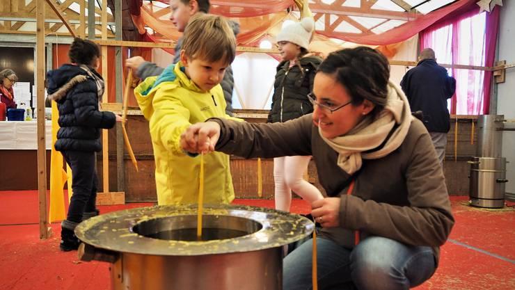 Nicole Kussmaul und ihr vierjähriger Sohn Noa tauchen den Docht in den Topf mit warmen Wachs.