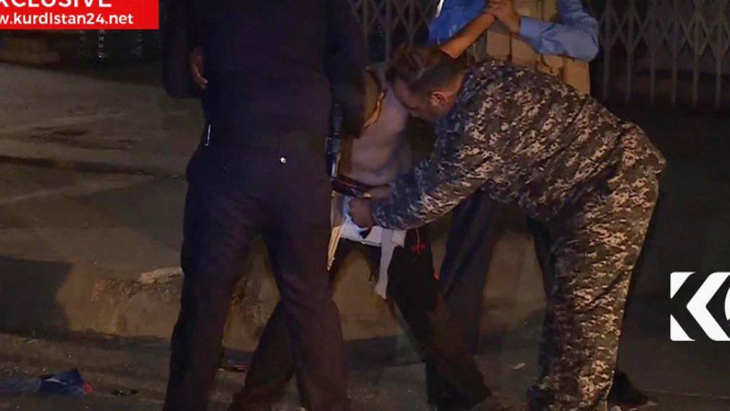 Zwei kurdische Sicherheitskräfte halten einen minderjährigen Selbstmordattentäter fest, während ein dritter den Sprengstoffgärtel entschärft. (Kurdistan 24 TV news)