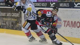 Fribourgs Benjamin Plüss (rechts) im Kampf um den Puck mit Timo Helbling