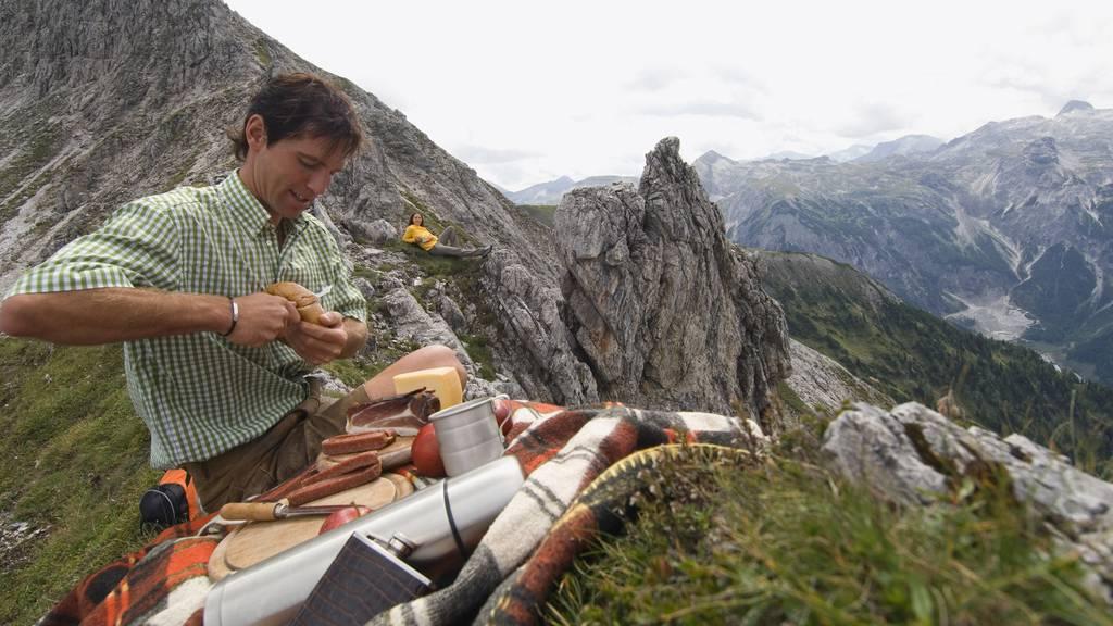 Dieser Mann isst Landjäger und Brot - Picknicken auf dem Gipfel geht aber noch viel ausgeflippter.