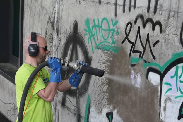 Ein Mitarbeiter der Stadtreinigung putzt mit Glaspudermehl unter Hochdruck Graffitis von den Wänden.