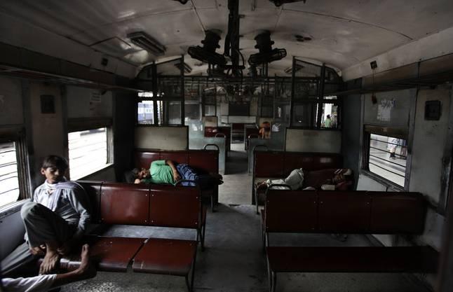 Pendler ruhen sich im Abteil eines stillgelegten Zuges aus