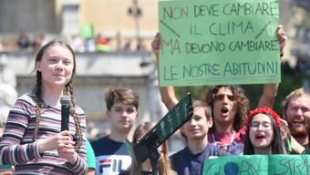 """""""Nicht das Klima muss sich ändern, aber unsere Gewohnheiten müssen es"""", halten Klima-Aktivisten in Rom in die Höhe, angeführt von der 16-jährigen Schwedin Greta Thunberg (links, mit Mikrophon)."""