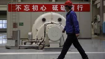 Ein Angestellter in einem chinesischen Produktionsbetrieb mit einer Schutzmaske.