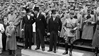 General Henri Guisan, Bundespräsident Eduard von Steiger, Bundesrat Karl Kobelt  und Bundesrat Enrico Celio (von rechts) auf dem Podest anlässlich der Fahnenehrung auf dem Bundesplatz in Bern am 19. August 1945.