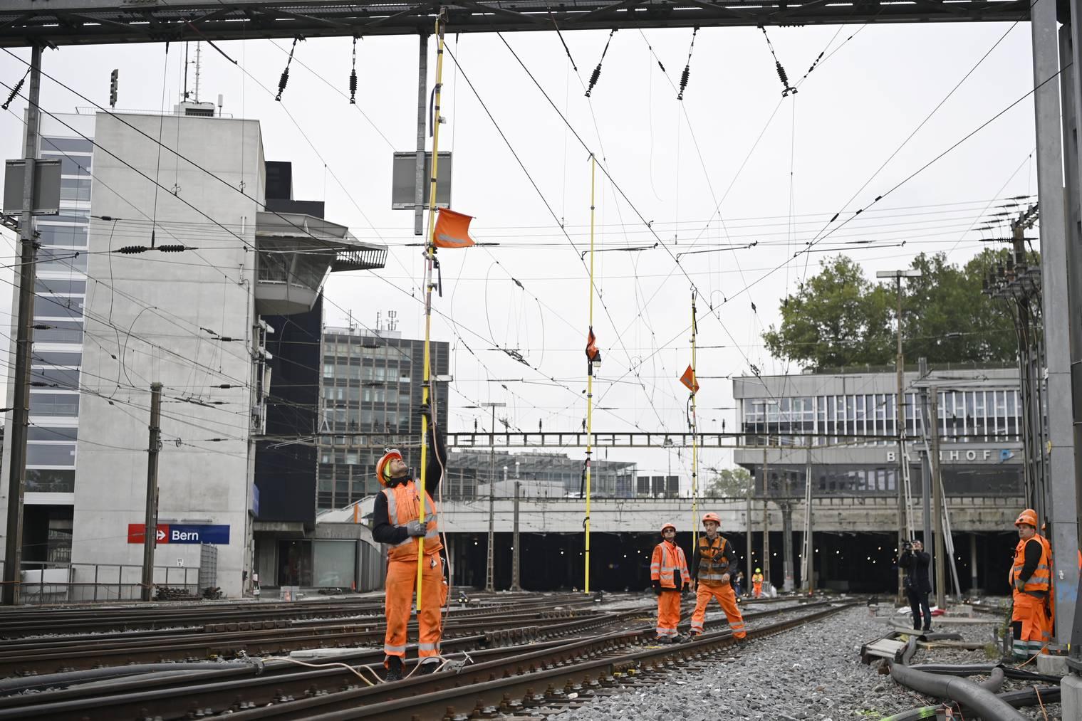 Bahnarbeiter reparieren die beschädigte Fahrleitung beim Bahnhof Bern.