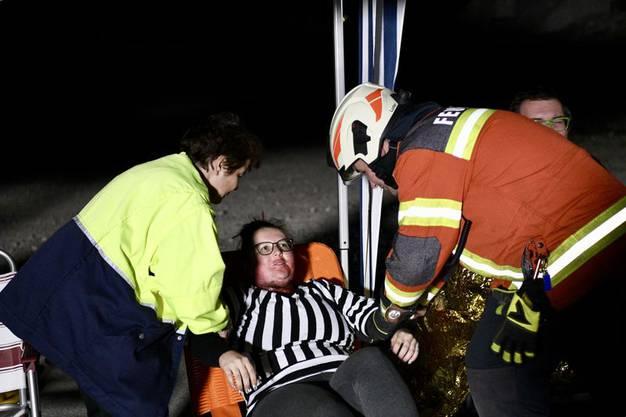 Eine Sanitätsdienstleistende und ein Feuerwehrangehöriger versorgen eine  Figurantin mit Verbrennungen.
