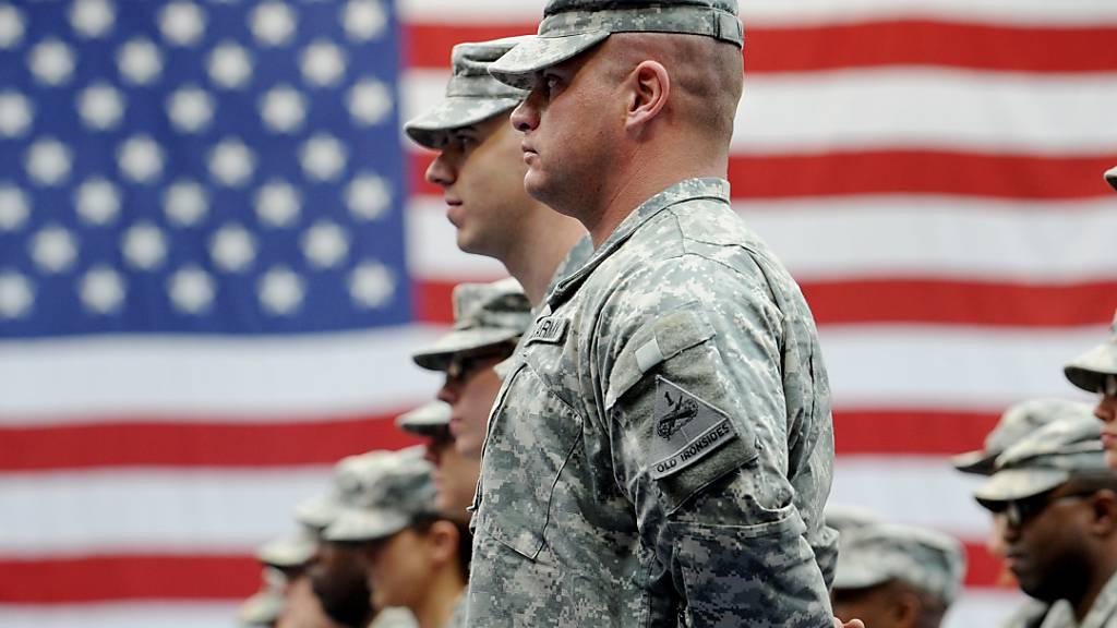 ARCHIV - US-Soldaten stehen nach ihrer Ankunft auf der US-Airbase in Wiesbaden-Erbenheim vor einer US-Flagge. Foto: Frank May/dpa