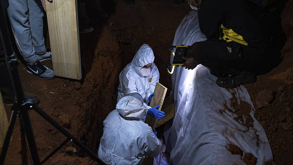 Menschen in Schutzkleidung nehmen in Johannesburg an einer Beerdigung einer an Corona gestorbenen Person teil. Südafrika ist eines der Länder auf dem Kontinent mit den meisten Todesfällen in Zusammenhang mit dem Coronavirus.
