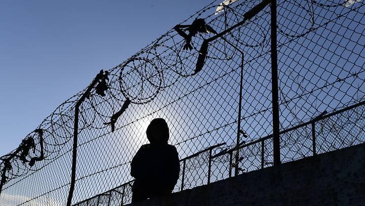 ARCHIV - Ein Migrant sitzt neben einem Zaun des Flüchtlingslagers Moria. Foto: Michael Varaklas/AP/dpa