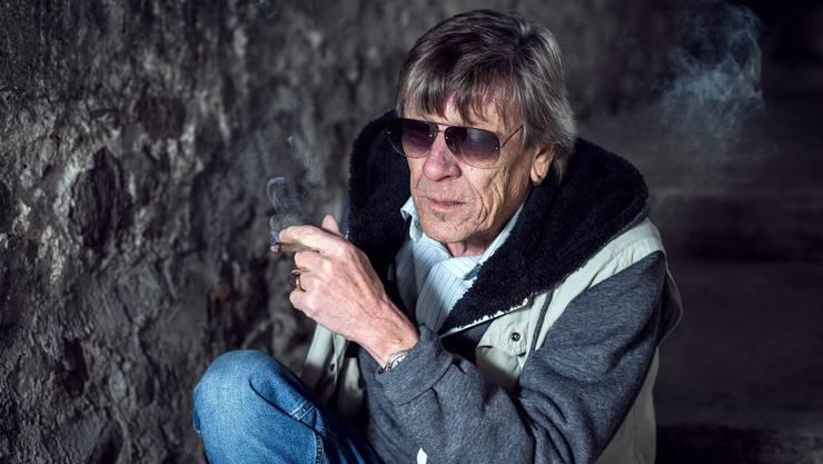 Polo Hofer posiert für ein Portrait und raucht dabei einen Joint.