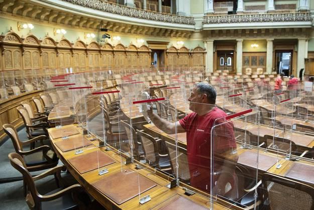 Ein Mitarbeitender putzt die Plexiglasscheiben im Nationalratssaal.