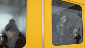"""Asiatische Touristen schauen aus einem stillstehenden Zug der Wengernalpbahn im Berner Oberland. Das """"Touristen-GA"""" blieb auch 2018 ein Renner. (Archivbild)"""