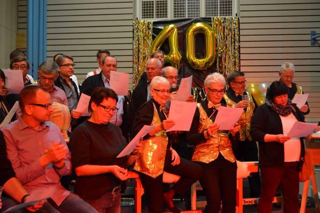 Gründungsmitglieder in den goldenen Kostümen werden auf die Bühne gebeten