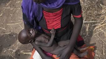 Eine süsudanesische Mutter wartet mit ihrer Tochter an einer Nahrungsmittelverteilstelle auf Essen. Etwa die Hälfte der Bevölkerung im Südsudan hat nicht genug zu essen. (Archiv)