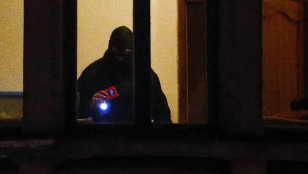 Sicherheitskräfte durchsuchen eine Wohnung. Ein Taxifahrer hat die Polizei auf die Spur der Attentäter gebracht und zu deren Wohnung geführt.