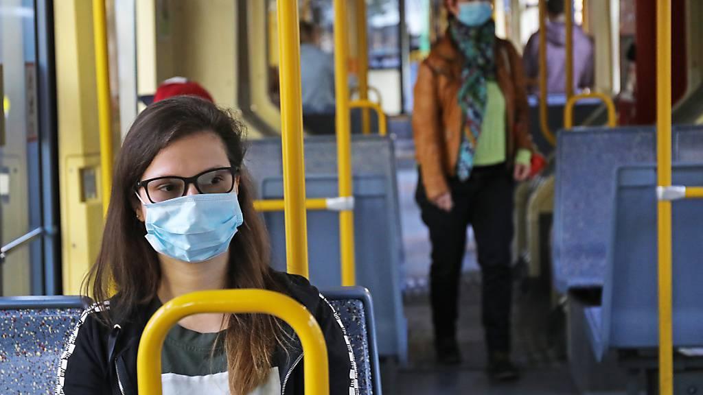 ARCHIV - Fahrgäste sitzen mit Schutzmasken in einer Kölner Straßenbahn. Foto: Oliver Berg/dpa