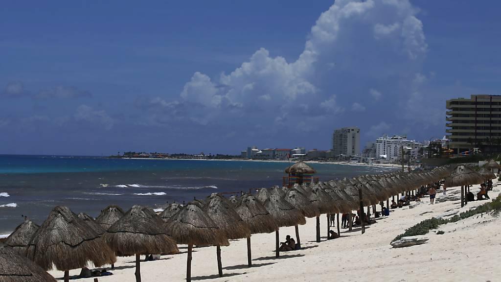 Touristen genießen den Strand vor der Ankunft des Hurrikans «Grace» in Cancun im mexikanischen Bundesstaat Quintana Roo. Wegen des herannahenden Hurrikans «Grace» sind im mexikanischen Touristenort Tulum die Hotels evakuiert worden. Die Gäste seien in Notunterkünften untergebracht worden. Foto: Marco Ugarte/AP/dpa
