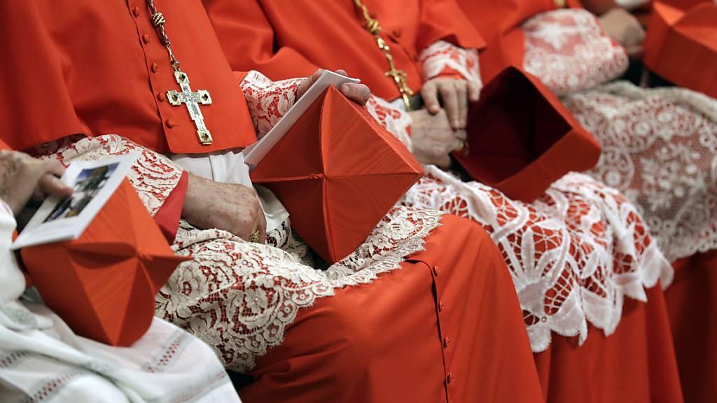 ARCHIV - Mehrere Kardinäle sitzen mit ihren Biretta-Hüten im Schoß in der Peterskirche. Wegen finanzieller Schwierigkeiten unter anderem durch die Corona-Pandemie hat Papst Franziskus die Gehälter von Kardinälen und Kurienchefs gekürzt. Foto: Andrew Medichini/AP/dpa - ACHTUNG: Dieses Foto hat dpa bereits im Bildfunk gesendet