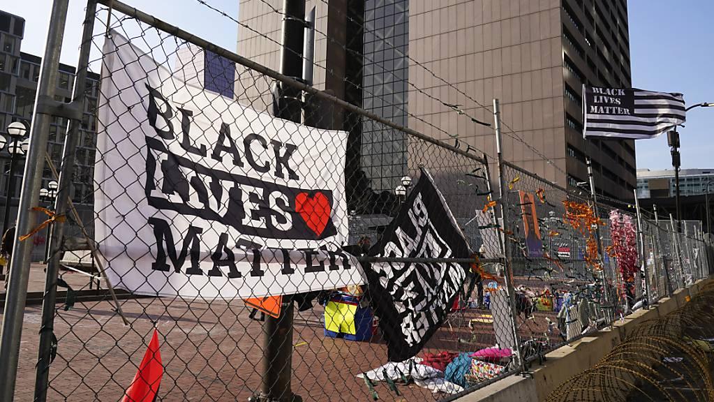 Fahnen und Plakate hängen am Zaun vor dem Regierungszentrum von Hennepin County, in dem der Prozess gegen den ehemaligen Polizisten Chauvin stattfindet.