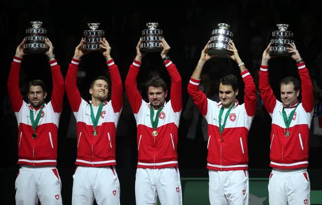 Michael Lammer, Marco Chiudinelli, Stanislas Wawrinka, Roger Federer and Coach Severin Lüthi halten die Trophäe in die Höhe.